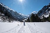Frau spaziert im Winter bei Sonne, blauem Himmel und Schnee durch das Bergpanorama des Stillachtals - Deutschland Oberallgäu Oberstdorf