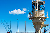 A historical signal light and the masts of a modern sailing ship with the cranes of a shipyard in the harbour, Kiel, Schleswig Holstein, Germany