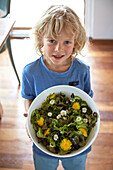 Boy holding a salad bowl with fresh herb salad