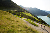 Couple with mountainbike riding up a road