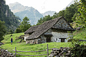 Young female hiker walking past an old house in the mountains, Valle Verzasca, Ticino, Switzerland