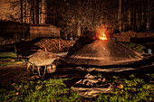 lit kiln with wheelbarrow and straw in front at night, charcoal production, Aalen, Baden-Wuerttemberg, Germany
