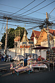 vendor sits in front of temple during market, Chiang Mai, Northern Thailand, Southeast Asia