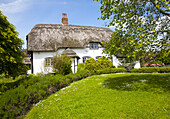 Pretty thatched country cottage in the village of Allington, Wiltshire, England