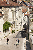 Two boys walking up the steep hill of Rue des Jacobins in Saintes.