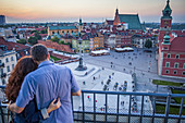 Couple, Plac Zamkowy square, The Royal Castle and Zygmunt column, View from Widokowy platform, Warsaw, Poland.