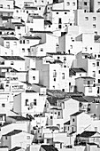 Houses seem to tumble down a steep hillside as if imitating a cubist painting, in the village of Casares, on the edge of the Sierra de Bermeja near Estepona in Southern Spain.
