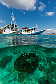 Local tourist boats anchored over underwater reef system on pink sand beach, Komodo National Park, Komodo Island, Indonesia.
