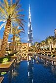 View of Burj Khalifa and Souq al Bahar at night in Downtown Dubai in United Arab Emirates.