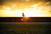 Healthy woman running at sunset.
