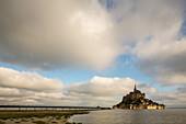 Abbey Mont-Saint-Michel, Unesco World Heritage, stilt bridge, 2014 new bridge for pedestrians and shuttle buses, clouds, renaturation, mudflats, low tide, tourist attraction, Normandy, France
