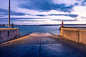 The beacon on the harbour wall. An empty slipway before the early morning boats start launching to go fishing. Still Bay, South Africa