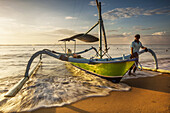 Fishing vessel with outriggers on beach at dawn, Sanur, Bali, Indonesia.