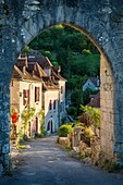 Setting sunlight on homes at entry gate to Saint-Cirq-Lapopie, Lot Valley, Midi-Pyrenees, France.