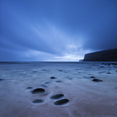 Clouds sweep across sky in fading light over beach at Rackwick Bay, Hoy, Orkney, Scotland.