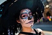 A young girl, dressed as â.La Catrinaâ., a Mexican pop culture icon representing the Death, walks through the town during the Day of the Dead celebration in Morelia, Michoacán, Mexico, 1 November 2014. Day of the Dead (â.Día de los Muertosâ.) is a syncret