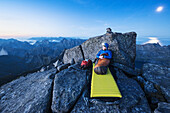 Open air mountain bivy on rocky summit of Hermannsdalstinden, Moskenesoy, Lofoten Islands, Norway.