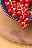 Closeup of red ripe redcurrant berries in a bowl.