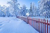 Red wooden fence, Wintertime, Jukkasjarvi, Lapland, Sweden. Cold temperatures as low as -47 celsius.