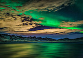 Aurora Borealis over Lake Kleifarvatn, Iceland. Cloudy evening with northern lights reflecting on the lake.