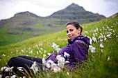 Young woman relaxing in the mountain fields of Kalsoy, Faroe Islands.