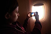 Young woman takes a photo through window during flight.