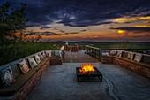 Campfire and woman enjoying the sunset, Etosha Safari Lodge, Etosha National Park, Namibia, Africa.