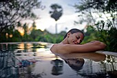 Young attractive woman enjoying a bath in the infinity edge swimming pool at The Dutch House, Galle, Sri Lanka.