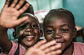 Local children waving happy into the camera, Sao Tome, Sao Tome and Principe, Africa