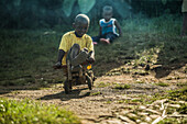 Little local boy riding on a simple wooden toy vehicle, Sao Tome, Sao Tome and Principe, Africa
