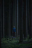 Young male runner standing in the forest and looking up, Allgaeu, Bavaria, Germany