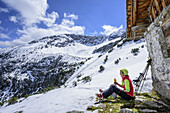 Woman back-country skiing having a break at alpine hut, Roter Stein, Fernpass, Lechtal Alps, Tyrol, Austria