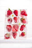 Presentation of a series of ice cubes with strawberries.