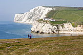 Couple walking hand in hand along the cliff tops on the west wight coastal route at freshwater on the isle of white UK.