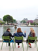 Friends relax around a fountain at the Tuileries Gardens (Jardin des Tuileries) in spring, Paris, France, Europe.