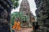 Monks visiting the Wat Banan. It is a small temple with five towers, which sits on top of a hill close to the Sanker river. Kantueu Pir commune, Banan district, Battambang province, Cambodia, Southeast Asia.