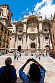 Tourists taking photos of the cathedral on Plaza de las Pasiegas square, Granada, Andalusia, Spain