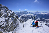 Two persons back-country skiing sitting at summit of Cresta Bianca, view towards Sorapis and Pelmo, Cresta Bianca, Monte Cristallo, Dolomites, UNESCO World Heritage Dolomites, Venetia, Italy