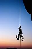 Young man rappeling with his mountain bike.