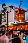 senior man taking a photograph of moulin rouge with an i pad, place pigalle, paris, ile de france, france.