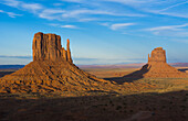 Monument Valley Utah desert mittens in panoramic of Western landscape at sunset Natioanal Park shadow of one mitten on another.