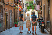 Tourists marvel at an alleyway in the Gothic Quarter of Barcelona, Catalonia, Spain.