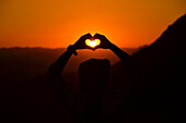 Silhouette of a man making a heart shape with his hands at sunset. Jordan, Wadi Rum desert, border with Saudi Arabia.