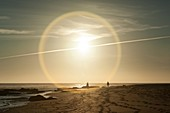 Sunset on sandy beach with halo around the sun and jet trail, Trafalgar beach, Cadiz, Spain