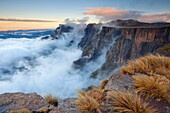 Landscape photo of the amphitheater wall in mist. Royal Natal National Park, Drakensberg, South Africa.