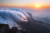 Landscape photo of clouds flowing over the twelve apostles in sunset light. Table Mountain, Cape Town, South Africa.