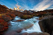 Landscape image of a waterfall below mount Fitz Roy in warm morning light. El Chalten, Patagonia, Argentina.