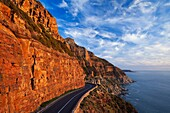 Wide angle photo of a dangerous mountain pass in red afternoon light. Chapmans Peak, Cape Town, South Africa.
