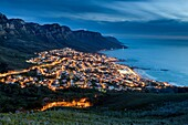 Landscape photo of a deep blue nightfall over a sparkling camps bay. Camps Bay, Cape Town, South Africa.