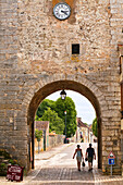A couple walk out of the old gate in the old part of Noyers sur Serein in Burgundy.